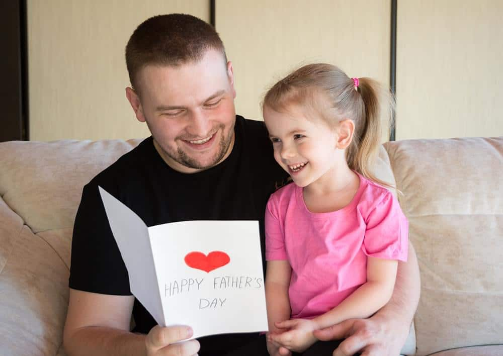 Father and daughter smiling and looking at a card
